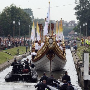 LONDON, ENGLAND - JULY 27: The Queen's rowbarge 'Gloriana' carries the Olympic flame along the river Thames from Hampton Court to City Hall on the final day of the London 2012 Olympic Torch Relay on July 27, 2012 in London, England. The Olympic flame is making its way through the capital on the final day of its journey around the UK before arriving in the Olympic Stadium tonight for the Olympic games' Opening Ceremony. (Photo by Oli Scarff/Getty Images)