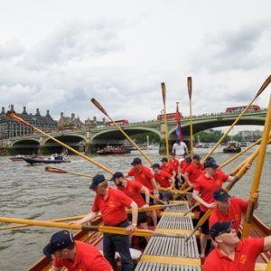 The crew of the Gloriana 'toss oars' as a salute to the Palace of Westminster